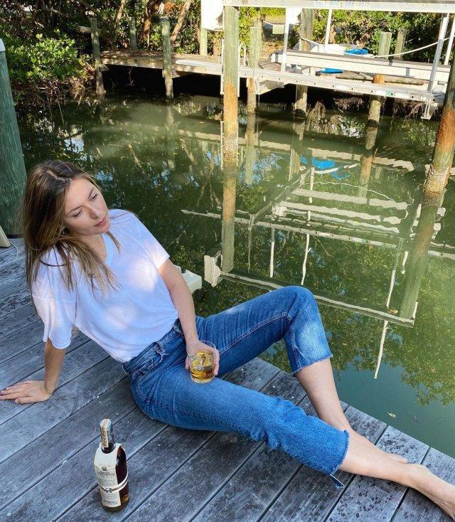 Мария Шарапова в белой футболке и джинсах пьет бурбон
