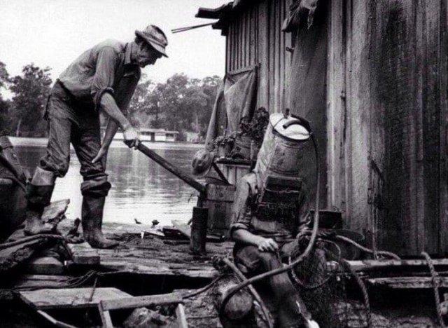 """Ловец жемчуга на Миссисипи готовится к очередному """"заходу"""". В качестве шлема - старый топливный бак от автомобиля. В нем он мог погружаться на глубину до 21 метра и быть под водой до 1,5 часа, 1938 год"""