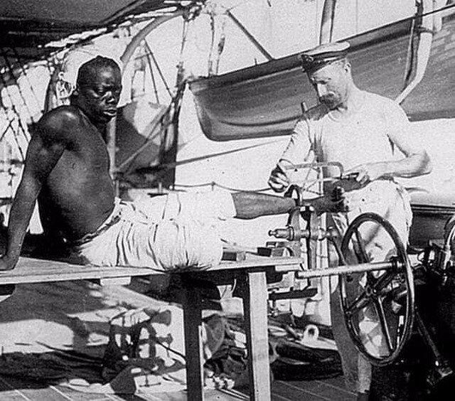 Британский моряк снимает кандалы с раба. Великобритания. Конец 19-го века.