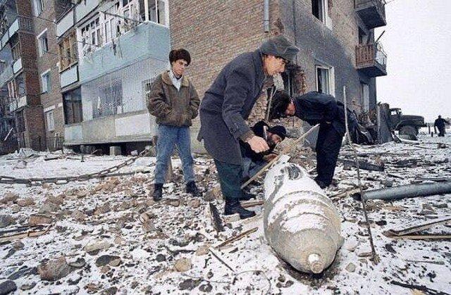 Чеченцы осматривают неразорвавшуюся бомбу после налета российской авиации на Аргун, 24 декабря 1994 года.