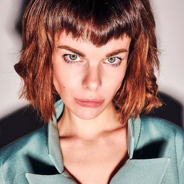 Анна Старшенбаум в зеленой рубашке и с челкой