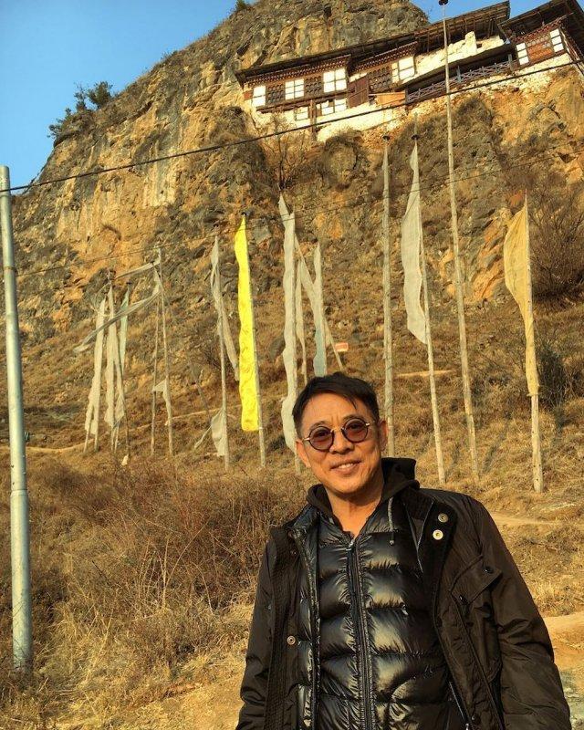 Джет Ли в очках стоит на улице