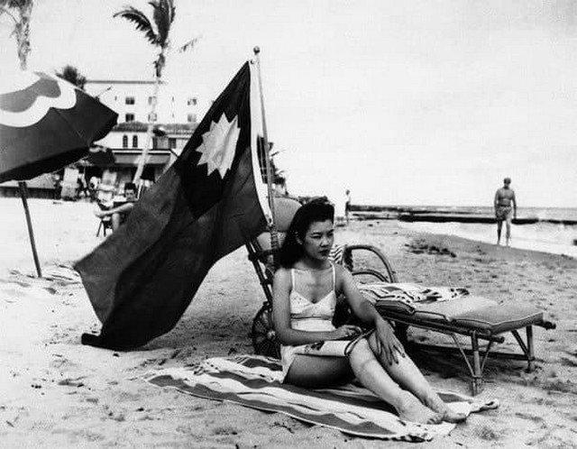 Oфициантка Руфь Ли загopaет под китaйским флагом, чтобы ee не приняли за японку, Maйами, 1941 год