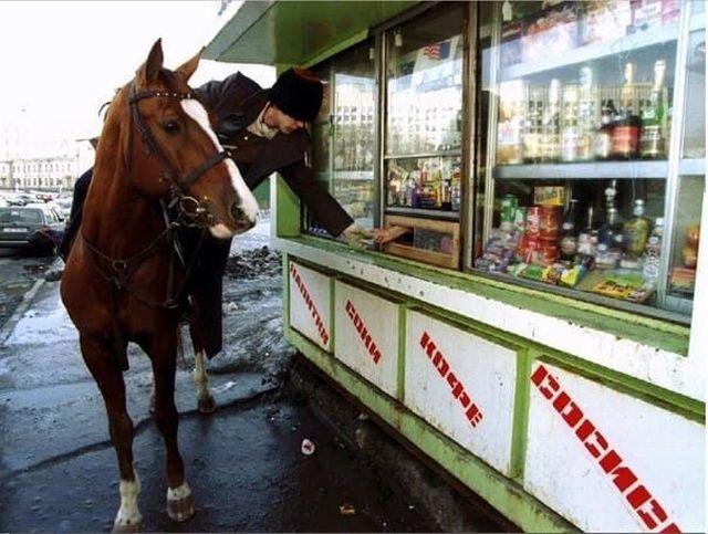 Казак на лошaди покупает бутылку водки в ларьке во время парада на День Святого Патрика, Москва, 1994 год.