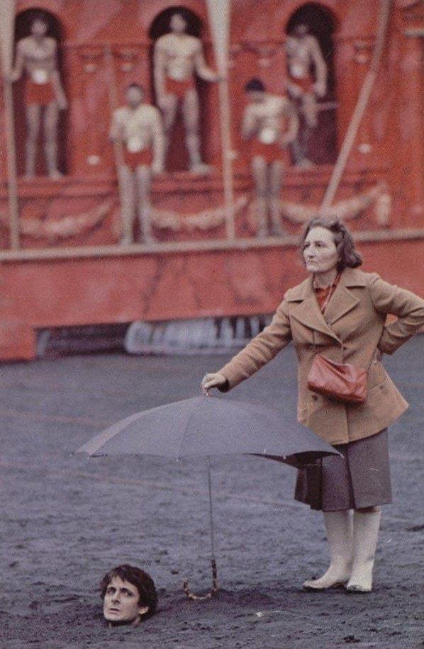 Ассистентка держит зонтик над головой актёра на съёмках «Калигулы» 1976 года