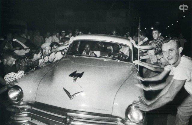 Толпа пытается перевернуть автомобиль с темнокожей семьей во время расовых беспорядков в г.Клинтоне. Теннесси. США. 1956 г.