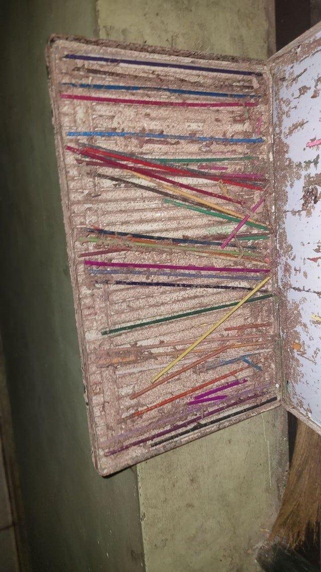 Старый пенал с карандашами после того, как термиты съели дерево