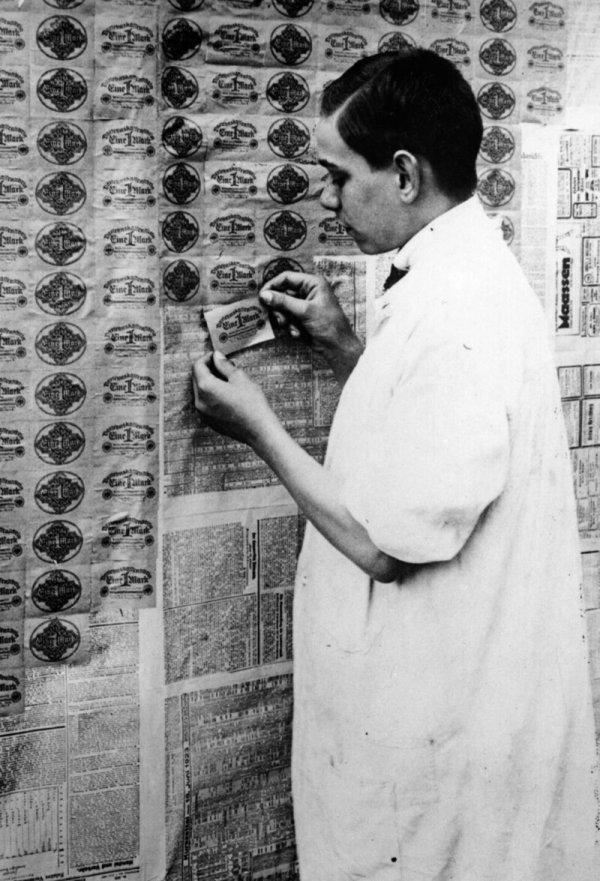 Мужчина использует банкноты номиналом 1 марка в качестве обоев. Более доступный вариант, чем даже самые дешёвые рулоны обоев, 1923 год