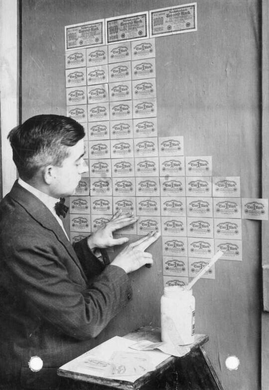 Житель Веймарской республики оклеивает стены обесценившимися банкнотами