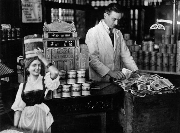 Владелец магазина кладёт лишние деньги в ящик для чая рядом с кассой, 1922 год