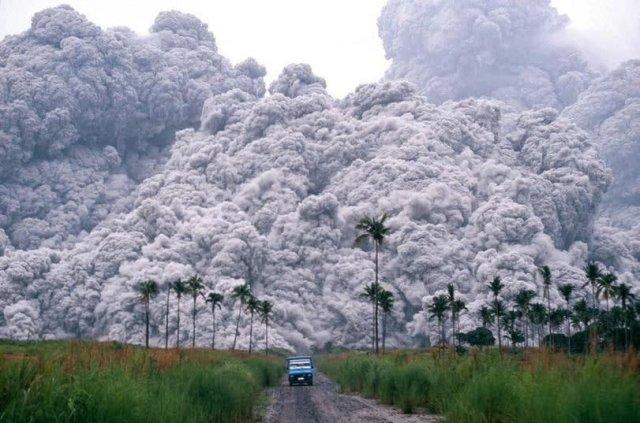 Водитель пикапа пытается сбежать от облака пепла, во время извержения вулкана Пинатубо на Филиппинах. 17 июня 1991 года.