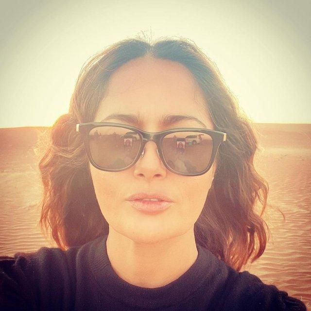 Сальма Хайек в очках и черной кофте в пустыне