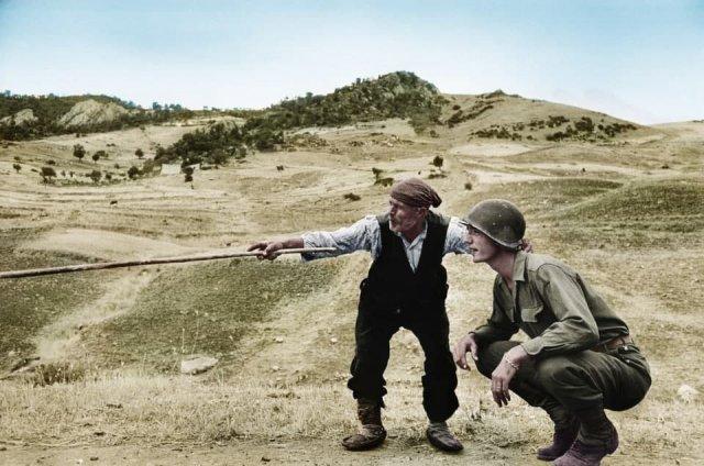 Сицилийский фермер показывает американскому солдату место отступления немцев. Август 1943 года.