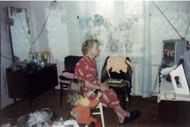 Бабушка с внучкой играет в приставку Dendy, джойстик у внучки не подключен. Россия, 1990-е годы.