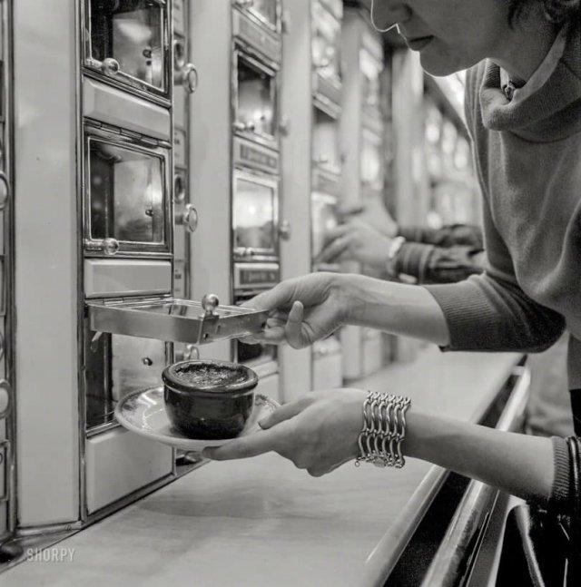 Женщина берет блюдо из запеченных бобов из автомата. Нью-Йорк, июль 1955 года.