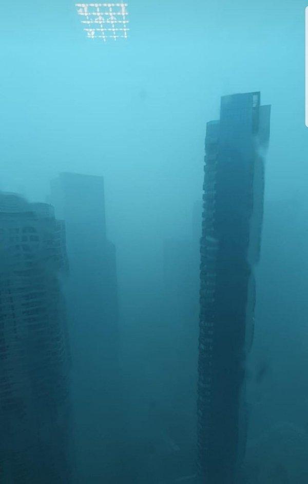 Вид из окна во время ливня, который выглядит как кадр из фильма о будущем