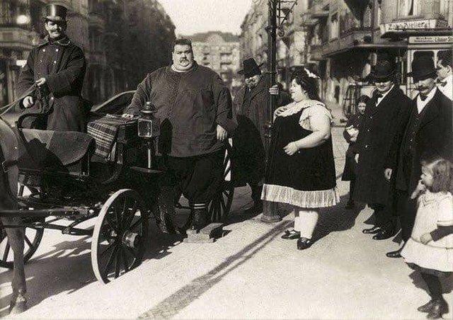 Полный мужчина (вес 284 кг) со своей женой (вес 174 кг) собирается на прогулку в конной коляске. Германия, 1912 год.