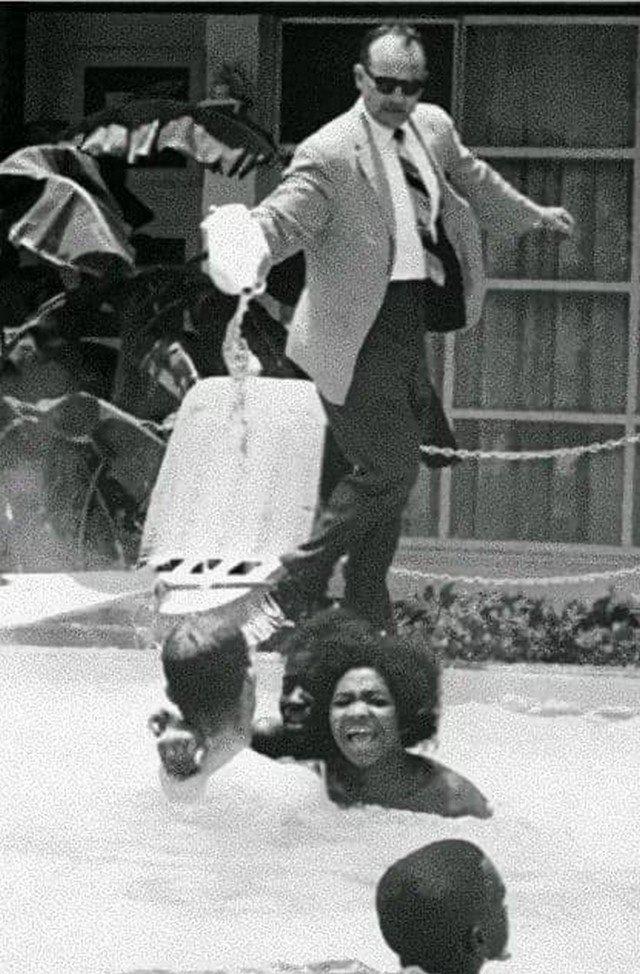 Менеджер отеля льёт отбеливатель в бассейн, в котором плавают чернокожие. США, 1964 год