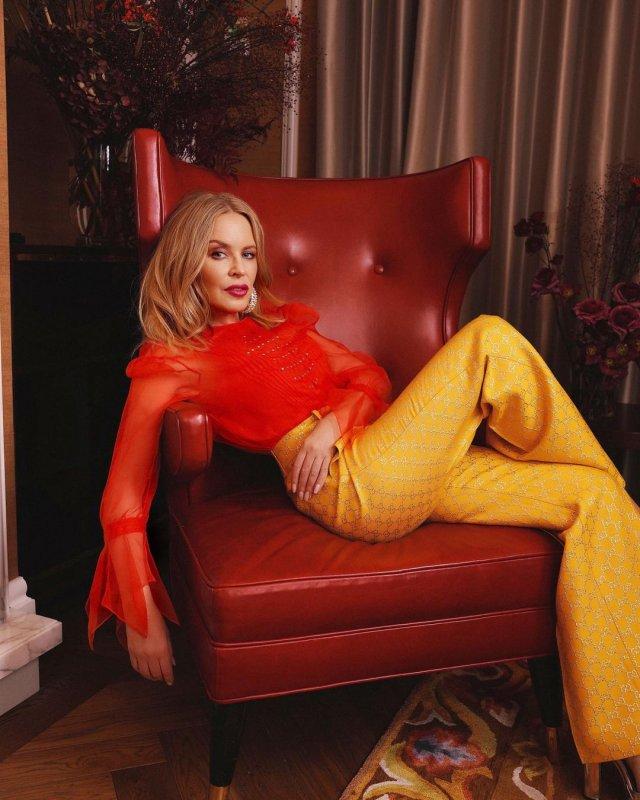 Кайли Миноуг в красной кофте и желтых штанах