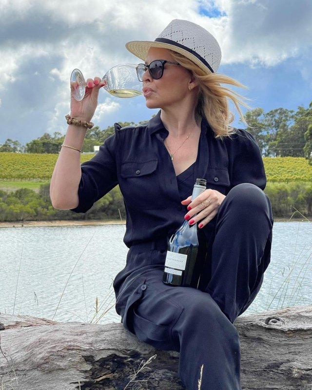Кайли Миноуг в черном костюме пьет вино