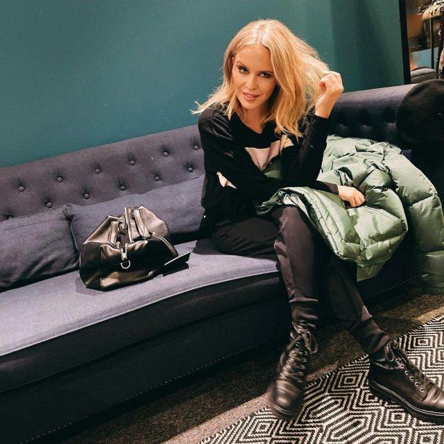 Кайли Миноуг в черном костюме на диване