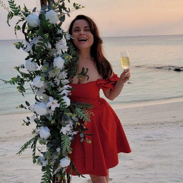 Певица Наташа Королева в красном платье у океана