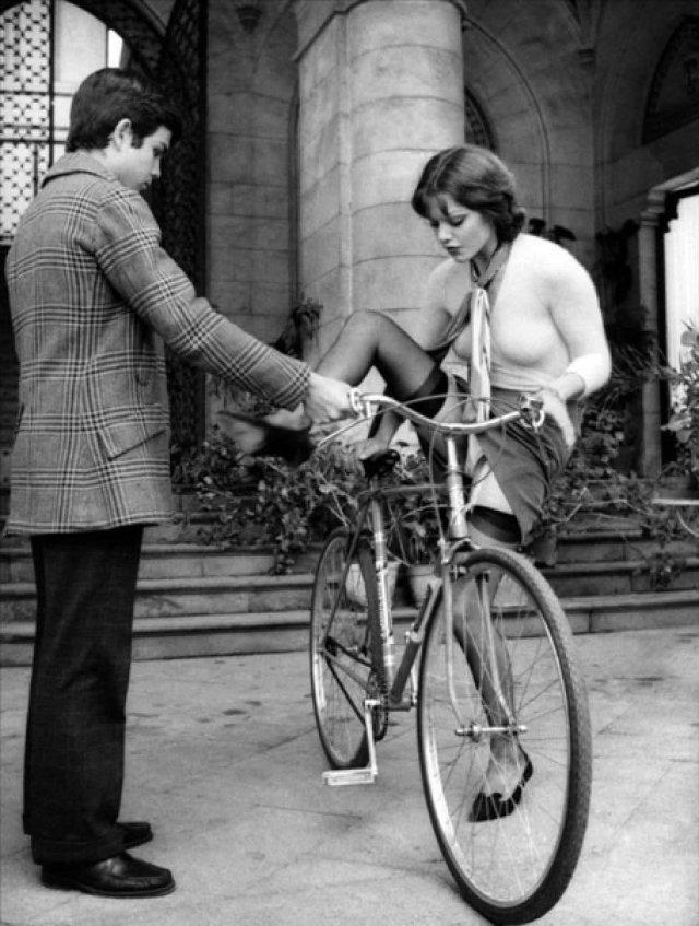Молодой человек галантно помогает даме взобраться на велосипед.Италия, 1973 г.