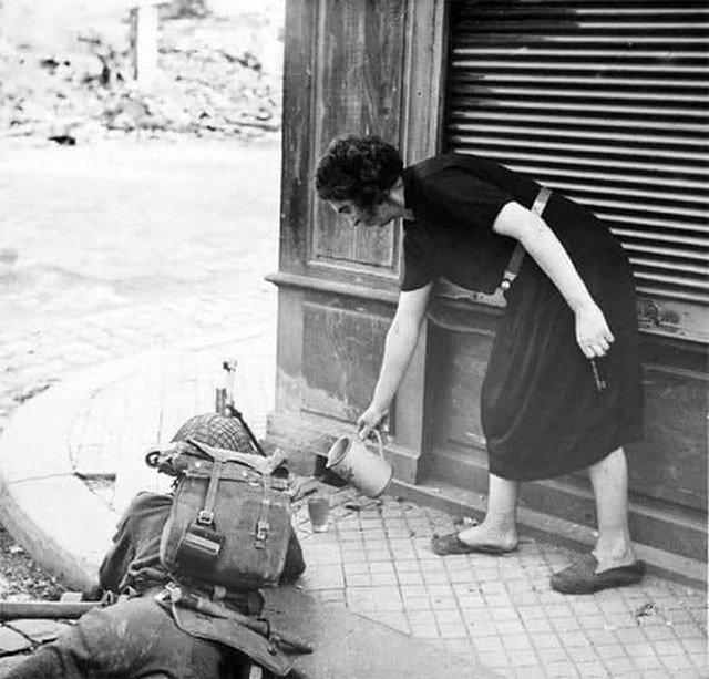 Француженка наливает чай британскому солдату, сражающемуся в Нормандии, 1944 год.