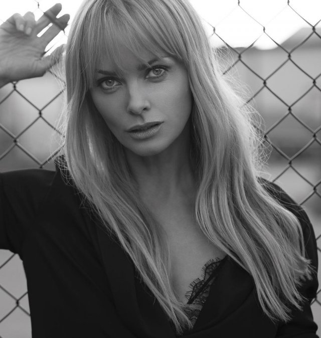 Изабелла Скорупко в черной кофте на фоне забора