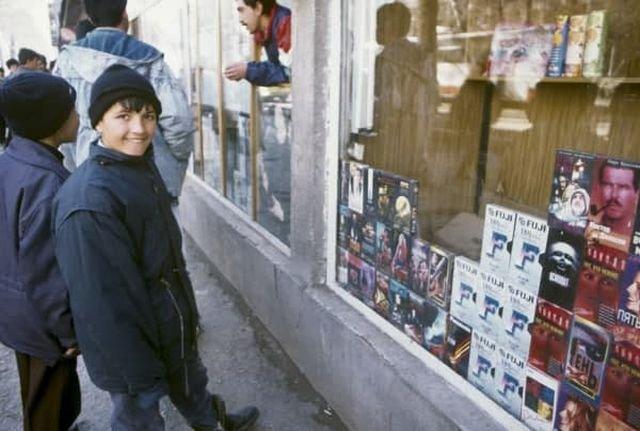 Таджикские дети возле витрины с фильмами на VHS кассетах, 1996 год.