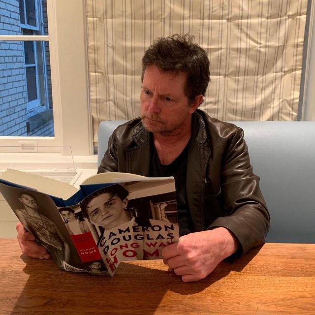 """Майкл Джей Фокс, звезда фильма """"Назад в будущее"""" читает книгу в кожаном костюме"""