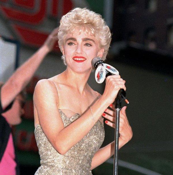Мадонна приветствует своих поклонников со сцены на Таймс-сквер в Нью-Йорке. 1987 год