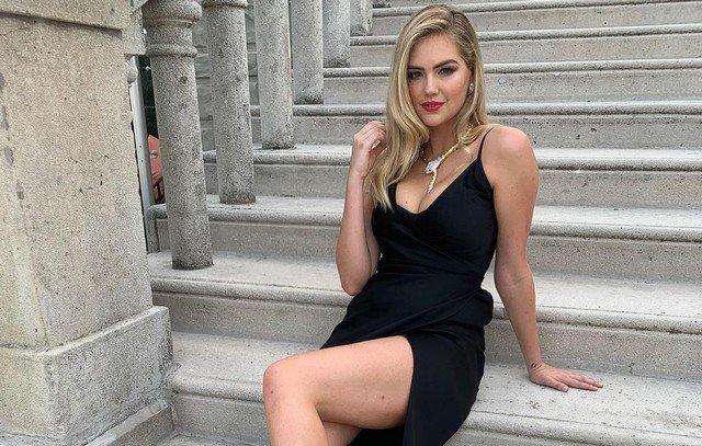 Кейт Аптон в черном платье сидит на лестнице