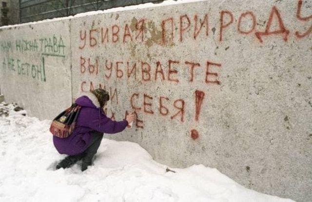 Жительница Москвы пишет на бетонном заборе