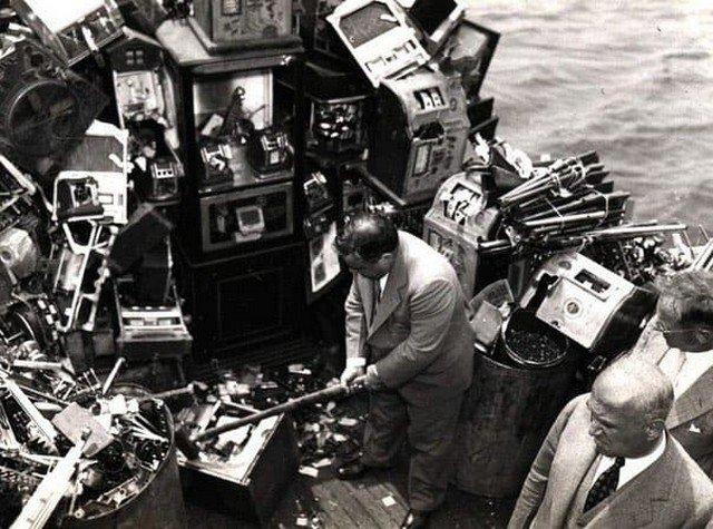 Мэр Нью-Йорка Фьорелло Ла Гуардиа разбивает кувалдой конфискованные игровые автоматы на борту полицейской лодки в Нью-йоркской гавани, 10 октября 1934 года.