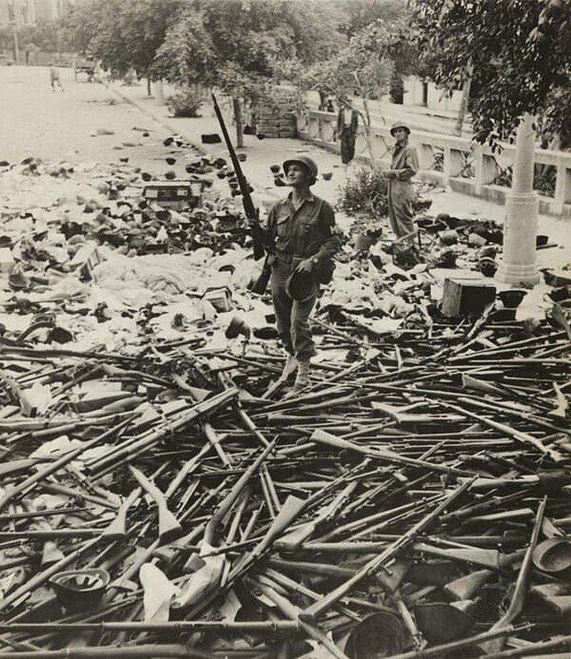 Солдат военной полиции США, стоящий на куче итальянских винтовок и шлемов после захвата Палермо, Сицилия, июль 1943 года.