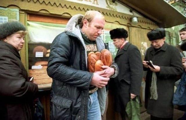Мужчина уходит от хлебного киоска с несколькими буханками хлеба