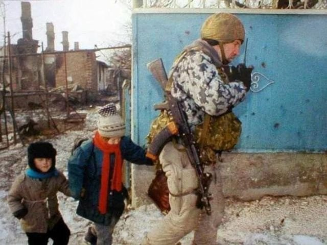 Боец ОМОНа ведёт обнаруженных в подвале дома детей к БТР. Грозный, февраль 1995 год.