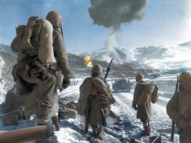 Солдаты морской пехоты США наблюдают за напалмовой бомбардировкой китайских позиций. 26 декабря 1950 года.
