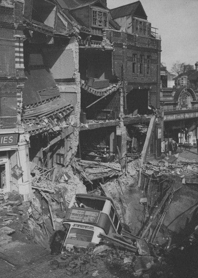 Двухэтажный автобус в бомбовой воронке у станции лондонского метро «Белхэм» (Balhem) после налета немецкой авиации.