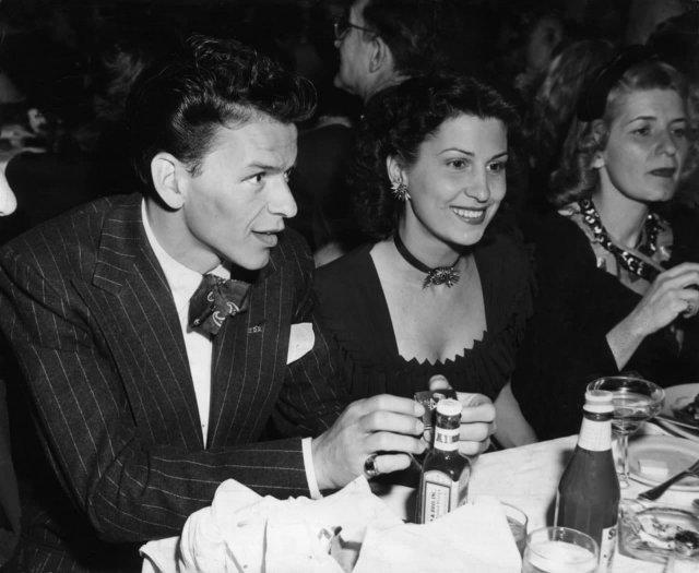 Фрэнк Синатра сидит за столом в ночном клубе рядом со своей первой женой, Нэнси Барбато, 1940 год. Они поженились в 1938 году.