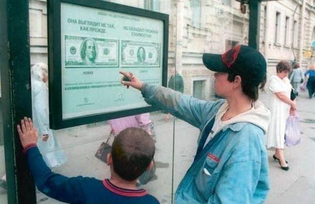Дети рассматривают памятку о новом дизайне 100–долларовой банкноты, размещённую на автобусной остановке, 1996 год, Москва