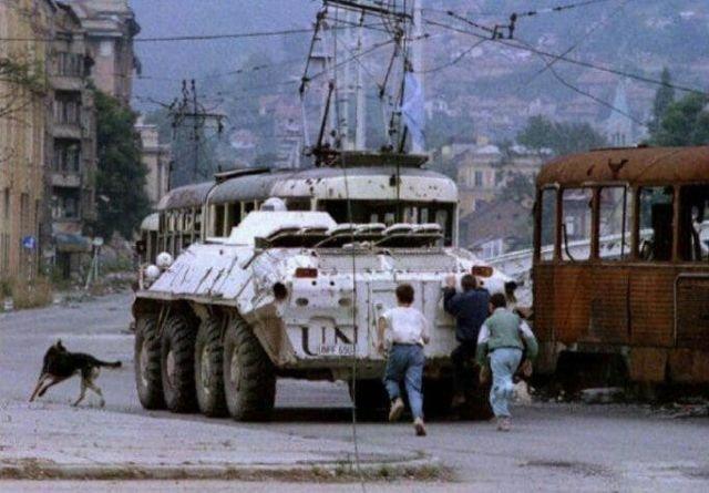 Три мальчика бегут за украинским бронетранспортером ООН, проезжающим мимо сгоревшего трамвая на площади Скендерия в осажденном Сараево 10 августа 1993 года.