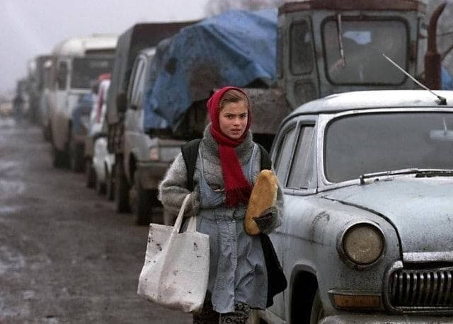 Девочка несёт буханку хлеба вдоль колонны беженцев, стоящих в очереди на контрольно-пропускном пункте у границы с Ингушетией, 27 декабря 1999 год.