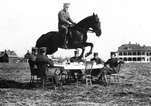 Американский офицер на лошади совершает прыжок через стол, за которым спокойно и небрежно сидят его сослуживцы.