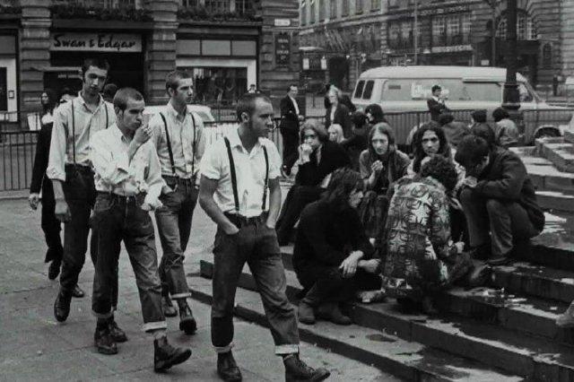 Площадь Пикадилли, Лондон, 1969 год, группа скинхедов проходит мимо группы хиппи