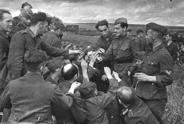Советский солдат дает сигареты немецким военнопленным, 1943 год.