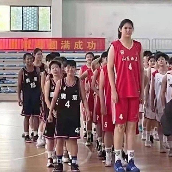14-летняя китайская баскетболистка рядом со своими менее высокими одноклассницами