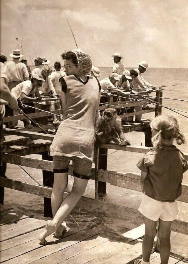 Девушка в купальнике старого образца с обезьянкой на пляже, 1949 год.