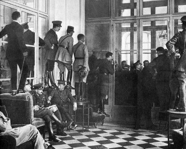 Люди стоят на кушетках, столах и стульях, чтобы увидеть подписание Версальского договора, официально завершившего Первую мировую войну, 1919 год.